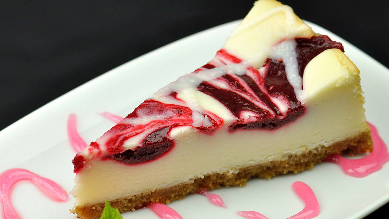 A fork slicing into a piece of cherry cheese cake